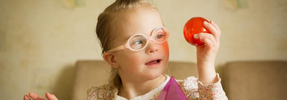 Young girl examining red ball